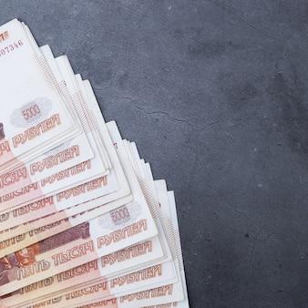 Grote stapel russische geldbankbiljetten van vijfduizend roebels die ventilator op een grijze cementachtergrond liggen.