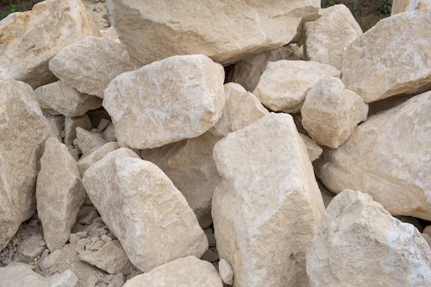 Grote stapel van grote zandstenen die op grond van bouwwerf leggen.