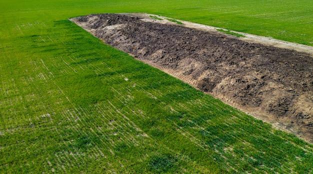 Grote stapel van organische meststoffen op het veld bovenaanzicht