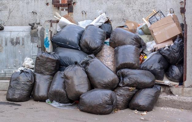 Grote stapel zwarte plastic vuilniszakken en dozen