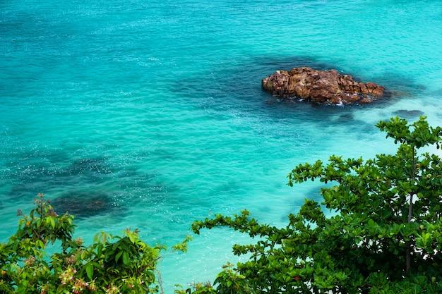 Grote stenen in de smaragdgroene zee de golf klopte langs de kust met bomen langs de kust in de andaman zee bij sunset beach, koh lipe, satun, zuid-thailand