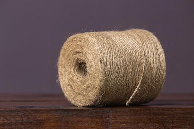 Grote streng bruin touw ligt op een houten plank op een effen achtergrond