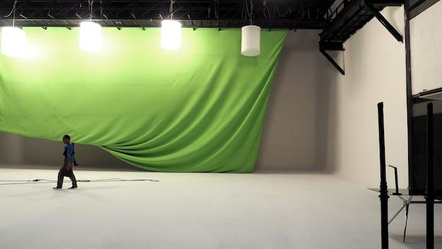 Grote studio met groen scherm en lightman en softbox licht hangend en witte vloer.