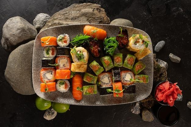 Grote sushi set. een gerecht uit de japanse keuken. sushirolletjes met chuka salade, zalm, philadelphia maki met roomkaas, sashimi, gunkans met rode kaviaar, avocado en japanse tamago omelet