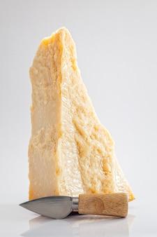 Grote taarten van parmezaanse kaas met klein kaasmes op witte achtergrond, verticale compositie