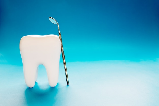 Grote tand en tandartshulpmiddel op blauwe achtergrond.