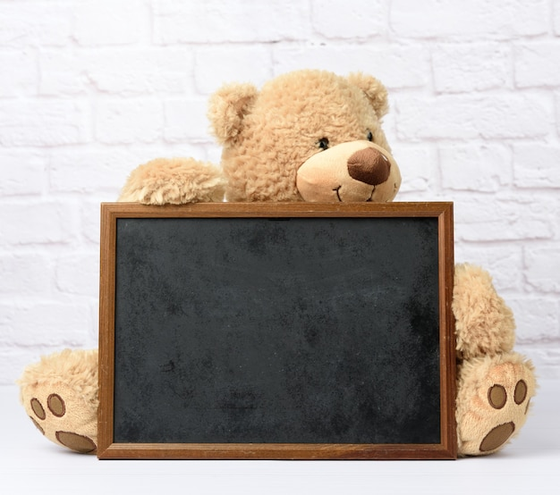 Grote teddybeer die leeg rechthoekig houten frame houdt