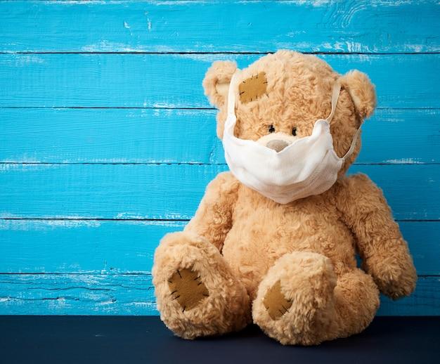Grote teddybeer zit in witte medische maskers