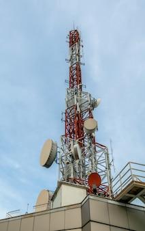 Grote telecommunicatietoren tegen lucht en wolken op de achtergrond