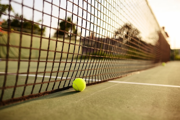 Grote tennisbal bij het net, niemand, buitenbaan. actieve gezonde levensstijl, sportspel met racketconcept