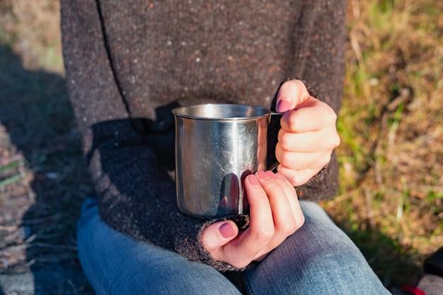 Grote toeristenbeker in vrouwelijke handen. close-up shot van een vrouw met een metalen beker buitenshuis