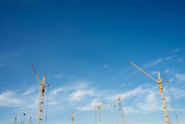 Grote torenkranen tegen de blauwe hemel.