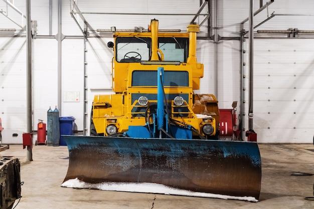 Grote tractor op wielen met een dozerblad voor het sneeuwvrij maken van wegen