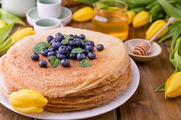 Grote traditionele russische pannenkoeken met bessen en honing op een houten tafel. bakken voor de voorjaarsvakantie vastenavond en een boeket gele tulpen. kopieer ruimte.