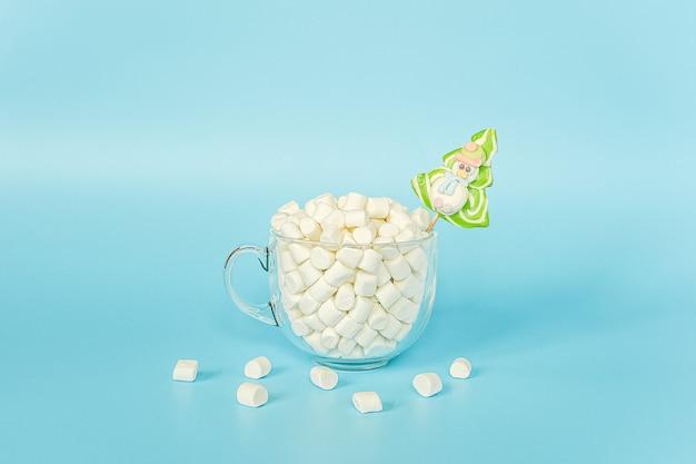 Grote transparante kop marshmallows met groene lollykerstboom op blauw