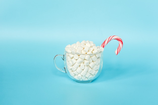 Grote transparante kop marshmallows met rood lollyriet op blauwe achtergrond