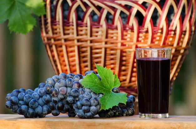 Grote tros rijpe druiven en een glas sap