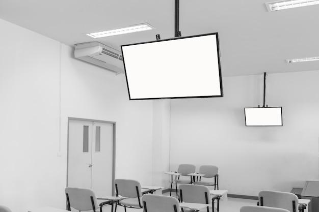 Grote tv-schermen hangen aan het plafond een klaslokaal
