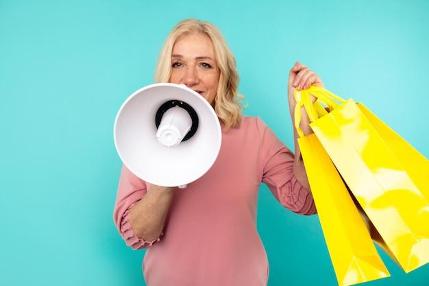 Grote uitverkoop. vrouw met luidspreker met boodschappentassen geïsoleerd.