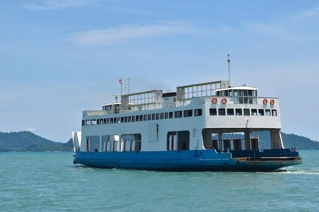 Grote veerboten die passagiers en auto's vervoeren die in blauwe zee oversteken tussen het eiland koh chang en de provincie trad, het concept van de levering van de vrachtlogistiek van thailand.