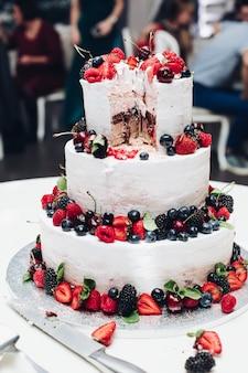 Grote verbazingwekkende bruiloft smakelijke cake met witte slagroom bedekt met verse, sappige bessen en fruit