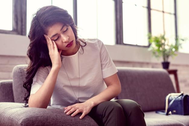 Grote vermoeidheid. leuke aantrekkelijke vrouw zittend op de bank tijdens het inslapen