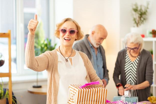 Grote verrassing. vrolijke oude vrouw die lacht terwijl ze een geschenkdoos in haar handen houdt