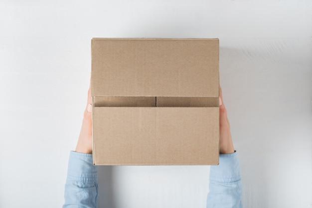 Grote vierkante kartonnen doos in vrouwelijke handen. bovenaanzicht, wit oppervlak