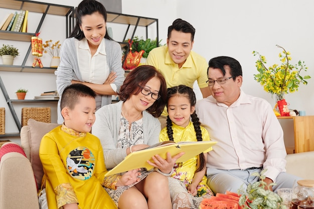 Grote vietnamese familie verzamelde zich thuis om oude foto's in fotoalbum te bekijken