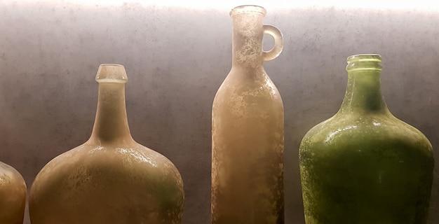Grote vintage vazen of kannen van gekleurd glas als decoratie-elementen in een modern interieur bij een grijze betonnen muur. decoratie van een appartement of huis.