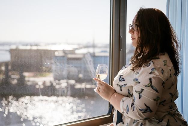 Grote vrouw voor het raam met een glas wijn, het concept van eenzaamheid