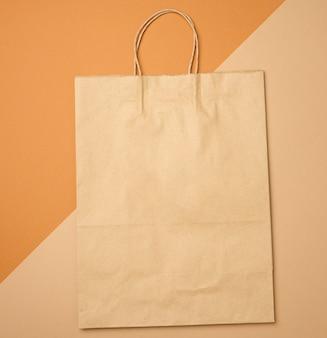 Grote wegwerp bruine kraft papieren zak met handvatten op een bruine achtergrond, eco-verpakking, geen afval