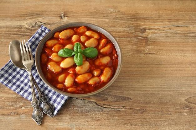 Grote witte bonen gekookt in tomaten en tomatenpuree in een bruine kom met basilicum op houten tafel