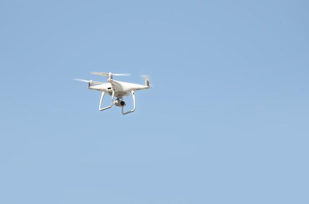 Grote witte drone die in een heldere blauwe hemel hangt