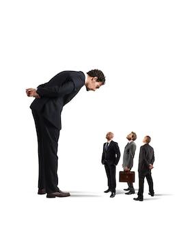 Grote zakenman die kleine zakenlieden kijkt. strenge baas vernedert zijn werknemers
