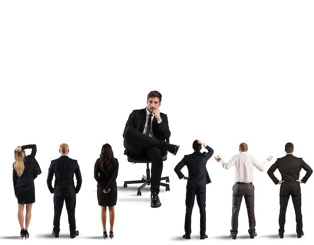 Grote zakenman zit in zijn fauteuil op zoek naar kleine zakenlieden