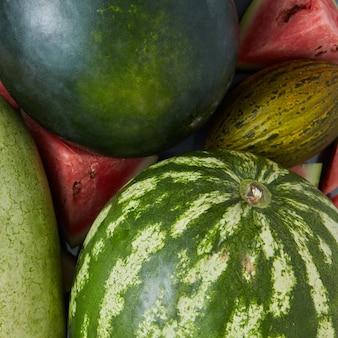 Grote zoete groene watermeloenen en plakjes watermeloen