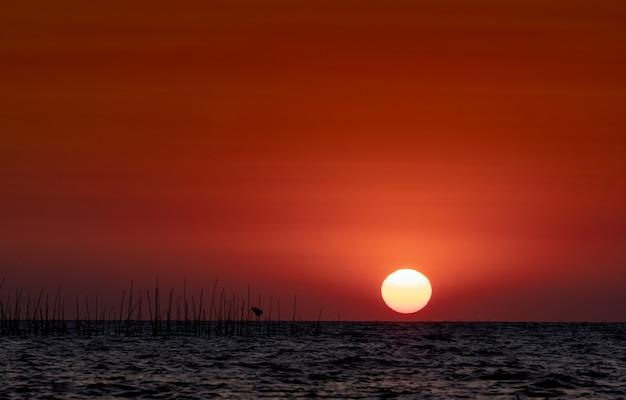 Grote zon over de zee bij zonsondergang. mooie zonsonderganghemel en horizon. rode romantische hemel voor vredig en rustig. inspiratie en offerte. schoonheid in de natuur. zomer strand scène. oceaan.