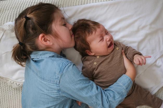 Grote zus kus huilende babymeisje op de bank. gelukkig gezin. thuis. dol zijn op. lief hoor. tederheid. grote zus. slow motion