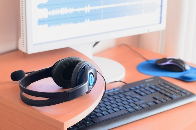 Grote zwarte koptelefoons liggen op het houten bureaublad van de sound designer