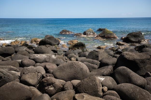 Grote zwarte stenen aan de oever van de indische oceaan. mauritius.
