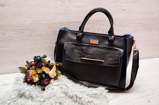 Grote zwarte vrouwelijke tas op een houten boeket bloemen, grijs kunstbont. in de mode