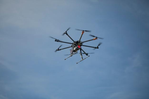 Grote zwarte zelfgemaakte krachtige hexacopter op een oppervlak van blauwe hemel, close-up