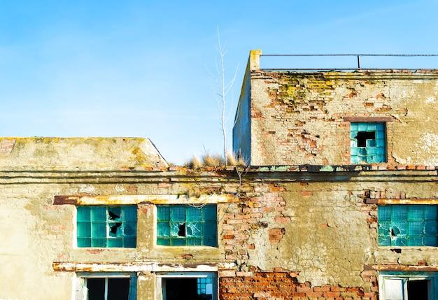 Grunge beschadigde gebroken ramen in bakstenen geruïneerde bouwmuur