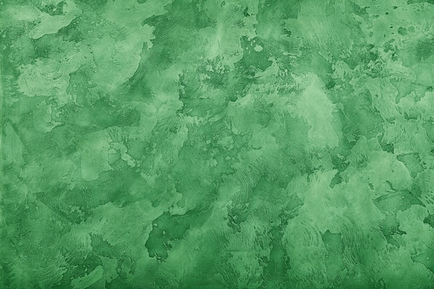 Grunge pastel groen vervaagde ongelijke oude leeftijd leem gips muur textuur achtergrond met vlekken en penseelstreken, close-up