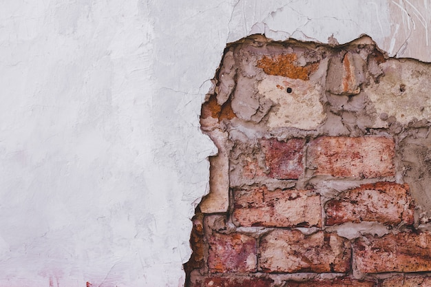 Grunge uitstekende bakstenen muurtextuur en witte gipspleister de achtergrond van de de bouwvoorgevel