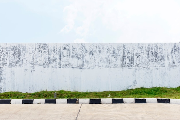 Grunge witte muur naast de straat met een blauwe hemelachtergrond
