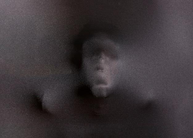 Gruwelijk gezicht achter doek