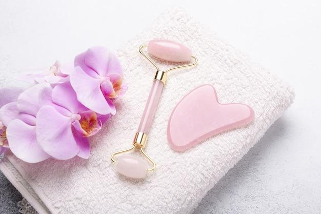 Gua sha massager en gezichtsroller op stenen achtergrond. massagetool voor gezichtsverzorging, spa schoonheidsbehandeling concept