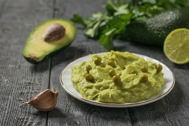 Guacamole, avocado fruit en knoflook op een zwarte houten tafel. dieet vegetarisch mexicaans eten avocado. rauw eten.